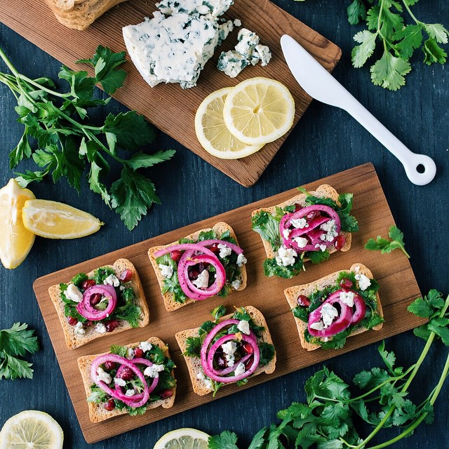 Whole Wheat Rusks Topped With Fresh Herb Salad, Pomegranate Seeds, Pickled Red Onion + Blue Cheese