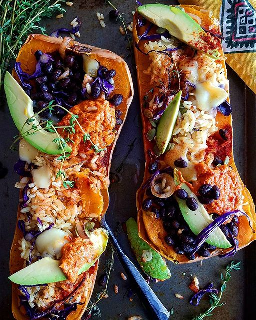 Roasted butternut squash stuffed with cumin black beans & rice topped with melted cheese, avocado…