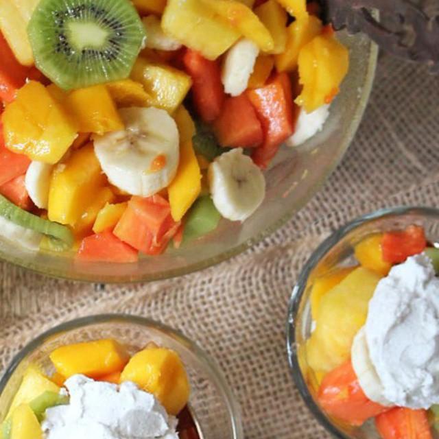 Sri Lankan fruit salad with papayas, pineapples,  mangoes, bananas and kiwi and topped with a…